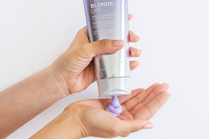 Blonde Life Violet Conditioner pouring into hand